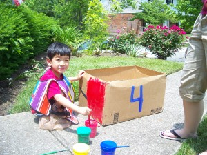Xander makes a train out of a box.